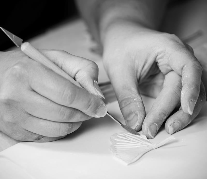 Kuvassa näkyy kädet. Toisessa kädessä on kynä ja toinen käsi pitää pienestä keramiikkatyöstä kiinni. Kuva on mustavalkoinen.