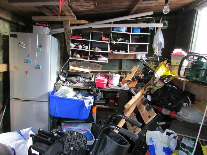 Kuvassa varastohuone, joka on täynnä sekalaista tavaraa. Huoneessa näkyy jääkaappipakastin ja sekalaisia laatikoita, koreja ja pusseja.
