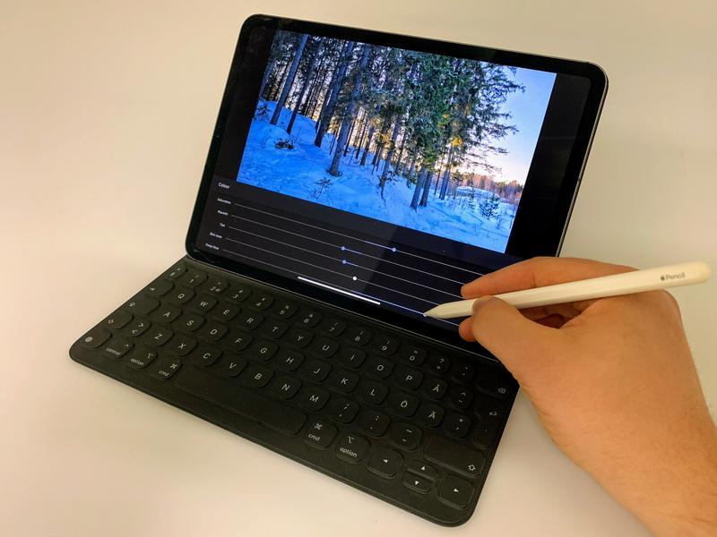 Tabletin sovelluksella muokataan talvista valokuvaa. Näytöllä näkyy valokuva metsämaisemasta ja kuva-arvojen säätimiä.